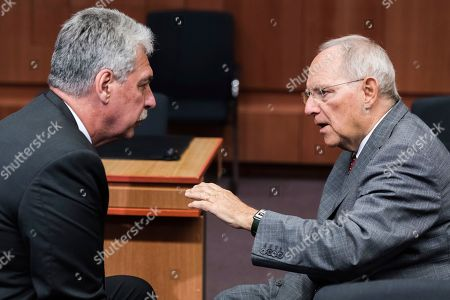 Stock Image of Austria's Finance Minister Hans Jorg Schelling, left, talks with Germany's Finance Minister Wolfgang Schauble prior to a meeting of Eurogroup finance ministers at the EU Council building in Brussels
