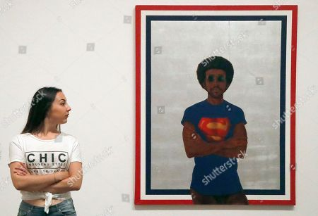 Stock Picture of A woman poses beside Barkley Hendricks painting, 'My Man Superman (Superman never saved any Black people)' at the exhibition Soul of a Nation, exploring the art made by African American artists between 1963 and 1983, in London,. The exhibition starts on July 12, 2017 and ends on Oct.22, 2017