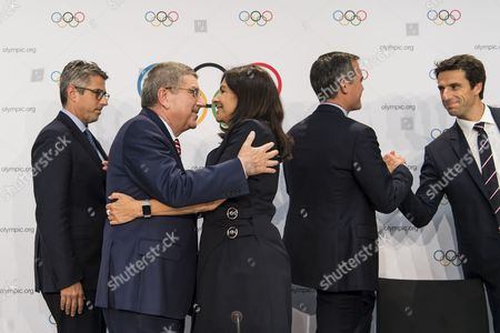 From left to right, Casey Wasserman, Chairman of Los Angeles 2024, International Olympic Committee, IOC, President Thomas Bach, from Germany, Anne Hidalgo, Mayor of Paris, Eric Garcetti, Mayor of Los Angeles, and Tony Estanguet, Co-president of Paris 2024, react during a press conference after the International Olympic Committee (IOC) Extraordinary Session, at the SwissTech Convention Centre, in Lausanne, Switzerland, Tuesday, July 11, 2017.