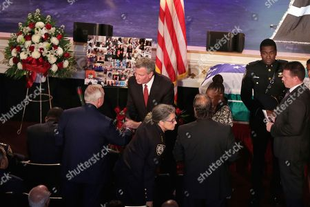 New York City Mayor Bill deBlasio, standing center, greets former New York City Police Commissioner William Bratton as he arrives for the funeral for New York City Police Officer Miosotis Familia, at the World Changers Church, in the Bronx borough of New York, . The slain officer was writing in her memo book last Wednesday when a man walked up to the police vehicle where she was sitting and fired