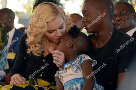 US musician Madonna, kisses one of her adopted daughters Stella, as son David Banda, right, looks on at the opening of The Mercy James Institute for Pediatric Surgery and Intensive Care, located at the Queen Elizabeth Central Hospital in the city of Blantyre, Malawi, . Madonna was in Malawi on Tuesday for the official opening of a hospital children's wing funded by her charity and named after one of the four children the pop star has adopted from the impoverished southern African nation