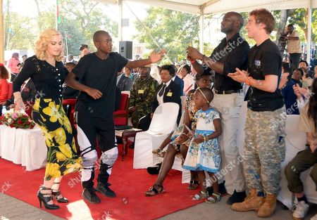 Stock Photo of US musician Madonna, left, dances with her adopted son David, second from left, at the opening of The Mercy James Institute for Pediatric Surgery and Intensive Care, located at the Queen Elizabeth Central Hospital in the city of Blantyre, Malawi, . Madonna was in Malawi on Tuesday for the official opening of a hospital children's wing funded by her charity and named after one of the four children the pop star has adopted from the impoverished southern African nation