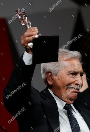 """Jose Carlos Ruiz holds aloft his best actor award for """"Almacenados"""" during the 59th Ariel Awards at the Palace of Fine Arts in Mexico City, . The Ariel Awards recognize excellence in motion picture making, such as acting, directing and screen writing in Mexican cinema"""