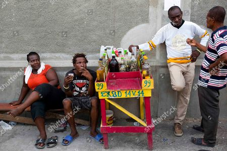 Stock Picture of Beneche Dadou Eddy Lecty, who sells the sugar-based alcoholic drink known as clairin, second from right, talks to a client as his relative Junior Lecty and local Suzie Bazil, left, sit nearby in the Cite Soleil area of Port-au-Prince, Haiti, . Eddy Lecty, who's selling spot has been coined by locals The Citizens Club, says people trust his product and former Haitians presidents like Rene Preval and Michel Martelly have stopped by to have a drink