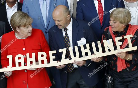 (L-R) German Chancellor Angela Merkel, German former alpine skier Christian Neureuther, and his wife German former alpine skier Rosi Mittermaier pose with members of the German Sports Aid Foundation (Deutsche Sporthilfe) during an official celebration on its 50th anniversary in the chancellery, in Berlin, Germany, 12 July 2017. The foundation helps and promotes German sportsmen and young talents nationwide and in international competitions.