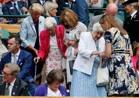Actress June Whitfield, center, is assisted to her seat in the Royal Box on Center Court for the Women's Singles semifinal match between Spain's Garbine Muguruza and Slovakia's Magdalena Rybarikova on day nine at the Wimbledon Tennis Championships in London