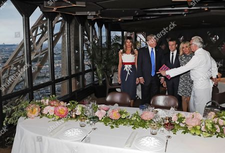 French chef Alain Ducasse (R) gestures as, from (2-R), Brigitte Macron, wife of French President Emmanuel Macron (C), US President Donald J. Trump (2-L) and First Lady Melania Trump (L) gather at the Jules Verne restaurant before a private dinner at the Eiffel Tower in Paris, France, 13 July 2017. US President Trump earlier arrived for an official visit to Paris.
