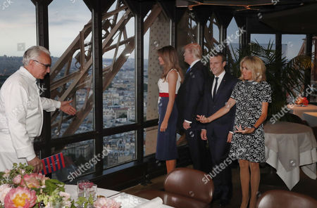 French chef Alain Ducasse (L) gestures as, Brigitte Macron (R), wife of French President Emmanuel Macron (2-R), US President Donald J. Trump (2-L) and First Lady Melania Trump (L) gather at the Jules Verne restaurant before a private dinner at the Eiffel Tower in Paris, France, 13 July 2017. US President Trump earlier arrived for an official visit to Paris.