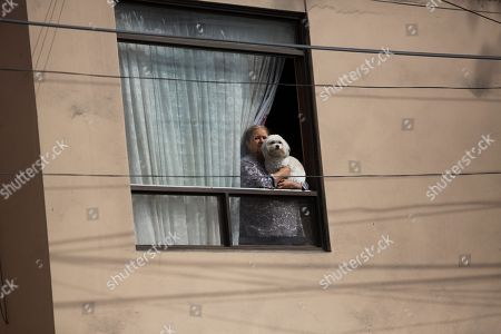 A woman, holding her dog, watches from her window the scene where Peru's former President Ollanta Humala and his wife Nadine Heredia leave the headquarters of Peru's National Party where they met with their lawyers, in Lima, . Prosecutors in Peru have requested the arrest of the former leader who governed Peru between 2011 and 2016 and his wife on money laundering and conspiracy charges tied to a corruption scandal involving Brazilian construction giant Odebrecht