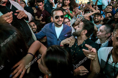 Indian actor Gulshan Grover, centre left, walks in between fans as he leaves the stage during The 18th edition of the International Indian Film Academy (IIFA) Awards event at Times Square, in New York