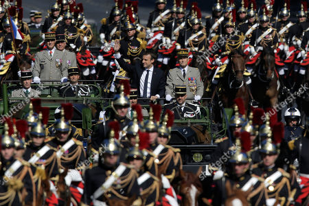 French President Emmanuel Macron, left, and Chief of the Defense Staff Gen. Pierre de Villiers, right, drive down the Champs Elysees avenue during Bastille Day parade in Paris, . Paris has tightened security before its annual Bastille Day parade, which this year is being opened by American troops with President Donald Trump as the guest of honor to commemorate the 100th anniversary of the United States' entry into World War I