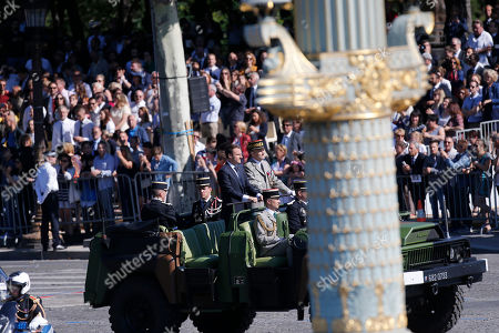 French President Emmanuel Macron, left, and Chief of the Defense Staff Gen. Pierre de Villiers, right, drive down the Champs Elysees avenue during Bastille Day parade in Paris