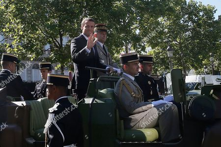 French President Emmanuel Macron, left, in the command car and Chief of the Defense Staff Gen. Pierre de Villiers, right, stand during Bastille Day parade in Paris, . Paris has tightened security before its annual Bastille Day parade, which this year is being opened by American troops with President Donald Trump as the guest of honor to commemorate the 100th anniversary of the United States' entry into World War I