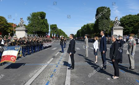 French President Emmanuel Macron (C) stands to attention along with French Prime Minister Edouard Philippe (R-4), French Defence Minister Florence Parly (R-5), French Army General Pierre de Villiers (R) and  French Junior Defence Minister Genevieve Darrieussecq (R-3) as they arrive to attend the annual Bastille Day military parade on the Champs Elysees avenue in Paris, France, 14 July 2017. Bastille Day, the French National Day, is held annually on 14 July to commemorate the storming of the Bastille fortress in 1789.