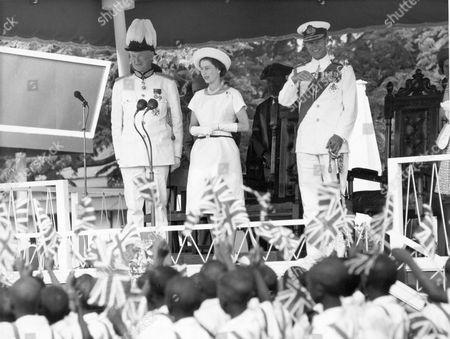 Stock Photo of The Queen (queen Elizabeth II) And Duke And Governor Of Gambia (sir Edward Windley) Stand On The Royal Dias In Macathy Square Bathurst And Acknowledge The Greeting Given Them By The Children. Lp3d Tour Of Gambia December 1961