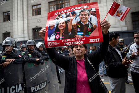 """A supporter holds a banner featuring Peru's former President Ollanta Humala and his wife Nadine Heredia with a message that reads in Spanish: """"Ollanta fullfilled! The president of inclusion"""", outside the Palace of Justice in Lima, . The former leader and his wife were taken into custody Thursday evening, after a judge ordered them held during an investigation into money laundering and conspiracy accusations tied to the scandal-tainted Brazilian construction giant Odebrecht"""