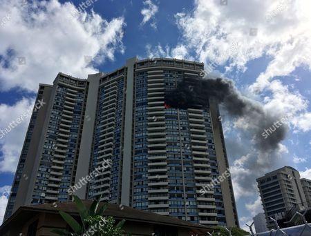 Smoke billows from a high-rise apartment building in Honolulu, . Dozens of firefighters are battling the multiple-alarm fire at Marco Polo apartments that Honolulu Fire Department spokesman Capt. David Jenkins said started on the 26th floor and has spread to other units