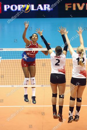 Stock Photo of Danielle Brisebois (C) of and Jennifer Cross (R) of Canada in action against Karina Ocasio (L) of Puerto Rico during the FIVB Women's Volleyball Grand Prix match between Puerto Rico and Canada at Roberto Clemente Coliseum in San Juan, Puerto Rico, 14 July 2017.