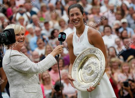 Spain's Garbine Muguruza is interviewed by Sue Barker as she holds the trophy after defeating Venus Williams of the United States in the Women's Singles final match on day twelve at the Wimbledon Tennis Championships in London