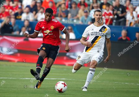 Marcus Rashford, Daniel Steres Manchester United's Marcus Rashford, left, shoots to score as he is followed by Los Angeles Galaxy's Daniel Steres during the first half of a friendly soccer match, in Carson, Calif