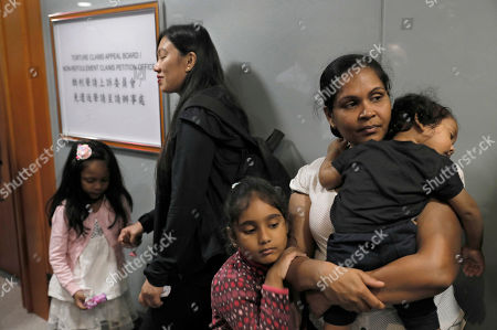 """Asylum seekers Nadeeka Dilrukshi Nonis, right, with her son Dinath and daughter Sethmundi Kellapatha and Vanessa Mae Rodel with her daughter Keana wait at the office of Torture Claims Appeal Board in Hong Kong . The Hong Kong lawyer for a group of refugees who sheltered former NSA contractor Edward Snowden four years ago said on Monday that the city's immigration department """"made systematic attempts"""" to detain the families"""