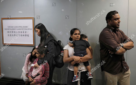 """Asylum seekers, from right, Ajith Pushpa Kumara, Nadeeka Dilrukshi Nonis with her son Dinath and Vanessa Mae Rodel with her daughter Keana and Nonis's daughter Sethmundi Kellapatha wait at the office of Torture Claims Appeal Board in Hong Kong . The Hong Kong lawyer for a group of refugees who sheltered former NSA contractor Edward Snowden four years ago said on Monday that the city's immigration department """"made systematic attempts"""" to detain the families"""