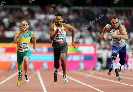 Scott Reardon of Australia (Left) on his way to winning gold in the Mens 100m T42 alongisde Richard Whitehead of Great Britain (right).