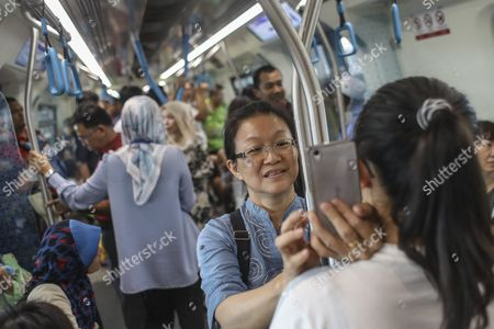 A woman (C) takes a selfie inside a train on the second phase of the first Mass Rapid Transit (MRT) Line at Kajang, Malaysia, 17 July 2017. The Sungai Buloh ? Kajang line spans 51km and has 31 stations out of which seven are underground. Malaysian Minister of Transport Liow Tiong Lai said on press statement on 17 July, that once the Semantan ? Kajang route is fully operational, the MRT Line 1 will transport an average of 150,000 passengers a day ? a drastic increase from the 15,000 passengers currently being transported.