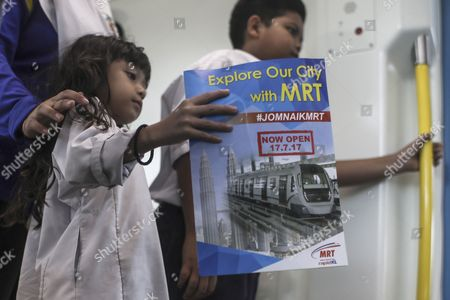 A young child carries a promotional poster while travelling on the second phase of the first Mass Rapid Transit (MRT) Line at Kajang, Malaysia, 17 July 2017. The Sungai Buloh ? Kajang line spans 51km and has 31 stations out of which seven are underground. Malaysian Minister of Transport Liow Tiong Lai said on press statement on 17 July, that once the Semantan ? Kajang route is fully operational, the MRT Line 1 will transport an average of 150,000 passengers a day ? a drastic increase from the 15,000 passengers currently being transported.