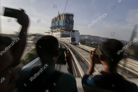 Stock Photo of Men take pictures of trains travelling on the second phase of the first Mass Rapid Transit (MRT) Line at Kajang, Malaysia, 17 July 2017. The Sungai Buloh ? Kajang line spans 51km and has 31 stations out of which seven are underground. Malaysian Minister of Transport Liow Tiong Lai said on press statement on 17 July, that once the Semantan ? Kajang route is fully operational, the MRT Line 1 will transport an average of 150,000 passengers a day ? a drastic increase from the 15,000 passengers currently being transported.