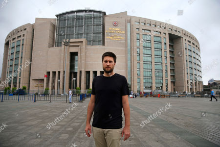Andrew Gardner, researcher on Turkey of Amnesty International, poses for the photographers outside Istanbul's court, . Ten Turkish human rights activists, including Amnesty International's Turkey director Idil Eser, who were detained by police while attending a training workshop appeared before a court in Istanbul on Monday to face possible charges or be released from custody