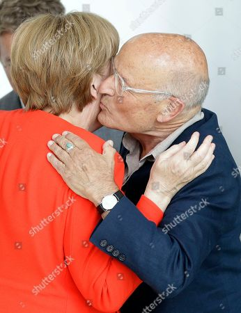 Director Volker Schloendorff, right, kisses German Chancellor Angela Merkel, left, during a reception for the round table 'Women in Culture and Media' at the chancellery in Berlin, Germany, . Merkel celebrates her 63. birthday on July 17