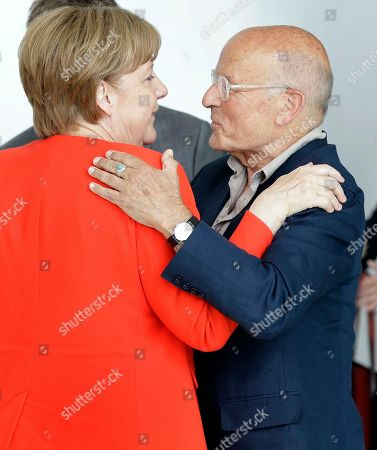 Director Volker Schloendorff, right, embraces German Chancellor Angela Merkel, left, during a reception for the round table 'Women in Culture and Media' at the chancellery in Berlin, Germany, . Merkel celebrates her 63. birthday on July 17