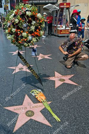"""A journalist photographs a wreath in memory of actor Martin Landau at Landau's star on the Hollywood Walk of Fame in front of the Dolby Theatre, home of the Oscars, . Landau, the chameleon-like actor who gained fame as the crafty master of disguise in the 1960s TV show """"Mission: Impossible,"""" then capped a long and versatile career with an Oscar for his poignant portrayal of aging horror movie star Bela Lugosi in 1994's """"Ed Wood,"""" died Saturday July 15, 2017. He was 89"""