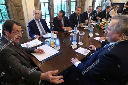 Nikos Kotzias, Nicos Anastasiades, Ioannis Kasoulides Cyprus' President Nicos Anastasiades, left, Greek Foreign Minister Nikos Kotzias, right, and Cyprus Foreign Minister Ioannis Kasoulides, rear left, sit during a meeting at the presidential palace in divided capital Nicosia, Cyprus, . Kotzias is in Cyprus for talks and he will attending the Cyprus' National Council meeting