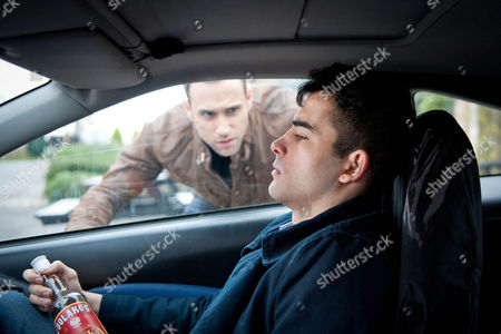 Stock Photo of Ep 7422 Thursday 11 February 2016 - 1st Ep Kirin Kotecha, as played by Adam Fielding, is clearly in turmoil and sits in the car drinking vodka. Nikhil Sharma, as played by Rik Makarem, tries to stop him from driving off but he speeds off, narrowly avoiding Brenda...