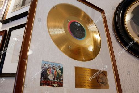 "A gold record presented to The Beatles for selling one million albums of ""Sgt. Pepper's Lonely Hearts Club Band,"" estimated at $10,000 to $15,000, is displayed at Gotta Have It! Collectibles, in New York, . An impending auction of pop star Madonna's personal items, including a love letter from her ex-boyfriend the late rapper Tupac Shakur, a pair of previously worn panties and a hairbrush containing her hair, was halted by a judge on Tuesday"