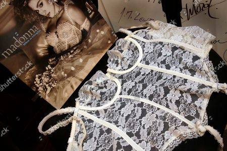 "The white lace corset worn by Madonna for the cover of her ""Like A Virgin"" album, estimated at $12,000 to $16,000, is displayed at Gotta Have It! Collectibles, in New York, . An impending auction of pop star Madonna's personal items, including a love letter from her ex-boyfriend the late rapper Tupac Shakur, a pair of previously worn panties and a hairbrush containing her hair, was halted by a judge on Tuesday"