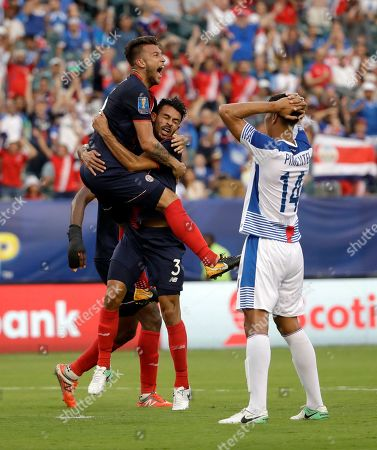 Costa Rica players celebrate an own goal in front of Panama's Valentin Pimentel (14) during a CONCACAF Gold Cup quarterfinal soccer match in Philadelphia
