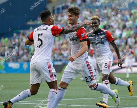 D.C. United midfielder Ian Harkes, center, is greeted by teammates Sean Franklin (5) and Lloyd Sam, right, after Harkes scored a goal against the Seattle Sounders during the first half of an MLS soccer match, in Seattle
