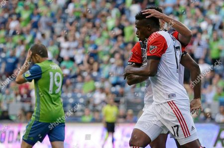 D.C. United forward Deshorn Brown, right front, is greeted by defender Sean Franklin as Seattle Sounders forward Harry Shipp reacts at left after Brown scored a goal during the first half of an MLS soccer match, in Seattle
