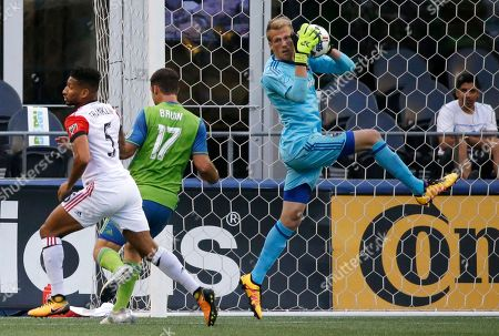 D.C. United goalkeeper Travis Worra, right, leaps for the ball near United's Sean Franklin, left, and Seattle Sounders forward Will Bruin (17) during the first half of an MLS soccer match, in Seattle