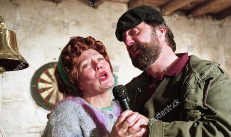 Nellie decides to have a party to celebrate their homecoming but no one except the Glovers, turn up. Zak and Butch unveil their surprise - a karaoke machine. With Zak Dingle, as played by Steve Halliwell, and Nellie Dingle, as played by Sandra Gough. (Ep 2025 - 9th November 1995).