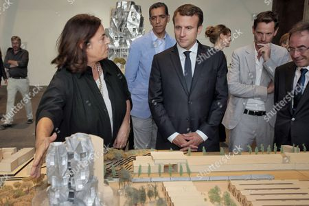 French President Emmanuel Macron (C) listens to Executive Director of the LUMA Foundation, Mustapha Bouhayati (2ndL) during a visit with Executive Director of LUMA Arles and President of the LUMA Foundation, Maja Hoffmann (L) to the LUMA Arles Foundation, as prefect of the Provence-Alpes-Cote d'Azur region, Stephane Bouillon (R), French Culture Minister, Francoise Nyssen (3rdL), Arles mayor Herve Schiavetti (2ndR) and President of the Executice Committee of the 'Rencontres d'Arles' annual photographic festival, Hubert Vedrine (Rear C) look on
