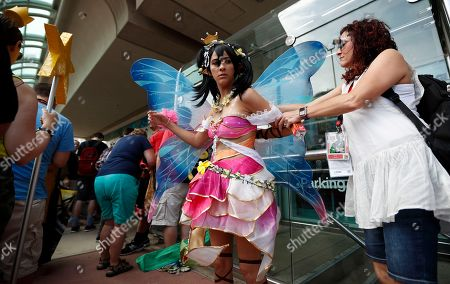 Stock Photo of Nancy Jones, dressed as Niko Yazawa, gets some help with her wings from Mary Beth Jones as they wait in line during the first day of Comic-Con, in San Diego. Comic-Con, which started as a comic-book convention with 300 participants in 1970 and has grown into a corporate-heavy media showcase that draws more than 130,000 attendees, runs through Sunday in San Diego