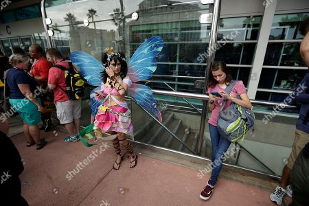 Nancy Jones, dressed as Niko Yazawa, waits in line during the first day of Comic-Con, in San Diego. Comic-Con, which started as a comic-book convention with 300 participants in 1970 and has grown into a corporate-heavy media showcase that draws more than 130,000 attendees, runs through Sunday in San Diego