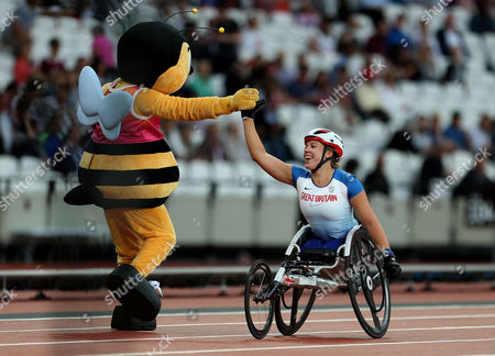 Hannah Cockroft of Great Britain celebrates after winning gold with the mascot in the Womens 400m T34 Final
