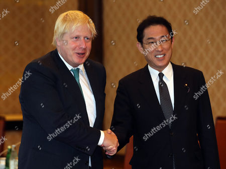 British Foreign Secretary Boris Johnson (L) shakes hands with his Japanese counterpart Fumio Kishida prior to their talks at the Iikura guesthouse in Tokyo