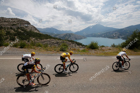 Britain's Chris Froome, wearing the overall leader's yellow jersey, Britain's Simon Yates, wearing the best young rider's white jersey, top left, France's Thomas Voeckler, left, and Spain's Mikel Landa, front, pass Serre-Poncon lake during the nineteenth stage of the Tour de France cycling race over 222.5 kilometers (138.3 miles) with start in Embrun and finish in Salon-de-Provence, France