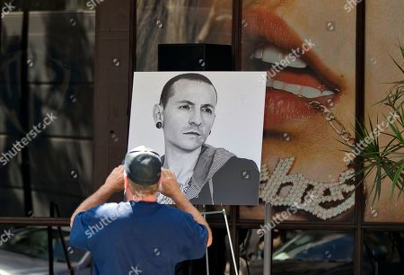 Fan David Gardner takes pictures of photographs of singer Chester Bennington, the frontman for the rock band Linkin Park, displayed on the front of the Warner Bros. Records offices in Burbank, Calif., . The Los Angeles County coroner confirmed Friday that Bennington, 41, died by hanging. He was found dead Thursday